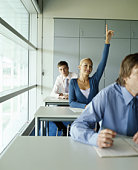 Woman raising hand in classroom, smiling