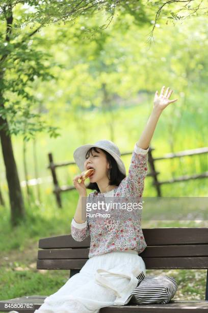 woman raising her left hand while eating bread
