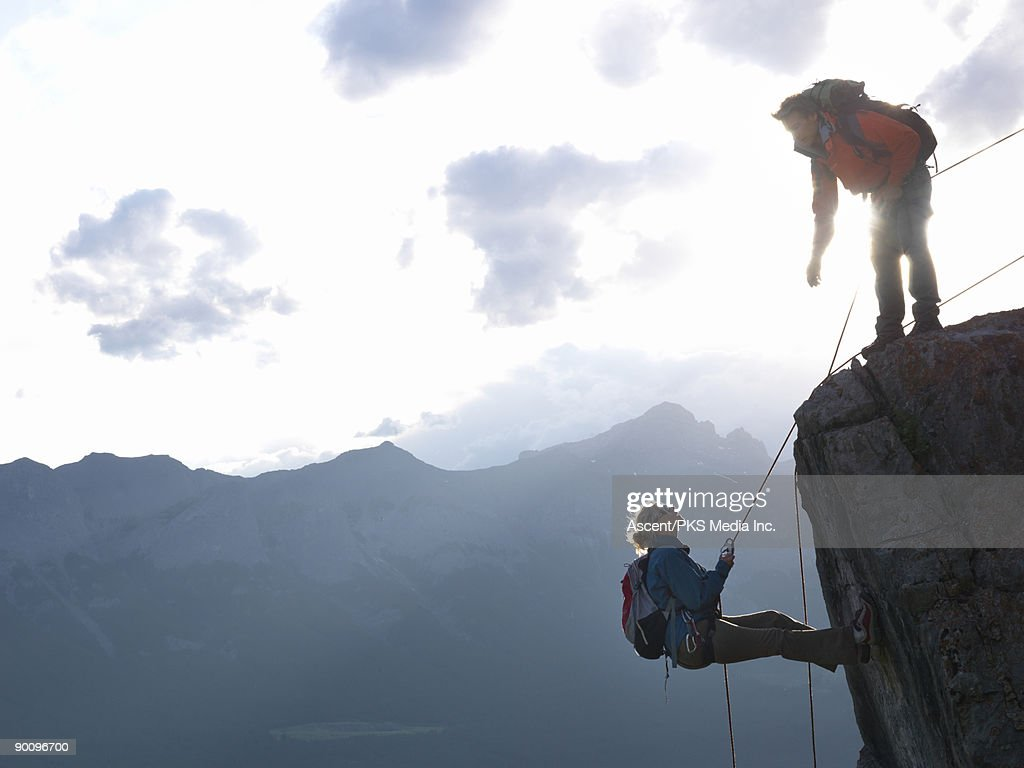Woman rappels (abseils) cliff, man directs on top : Stock Photo