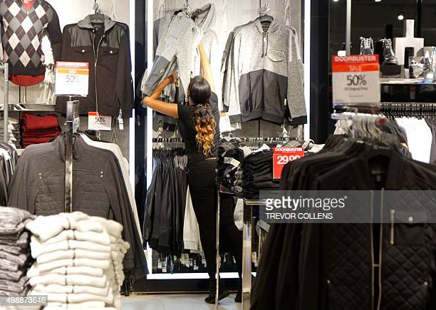 A woman reaches as she shops for clothes in Macys department store in Herald Square New York on November 26 2015 Many retail outlets opened their...