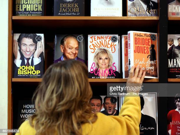 A woman reaches for a copy of Bridget Jones Mad About The Boy by Helen Fielding next to a copy of My Life by David Jason as in Waterstones in...