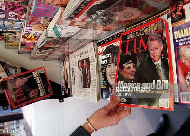 A woman reaches for a copy of Time Magazine on a news stand 26 January in New York NY The magazine issue which hit the stands 26 January features a...