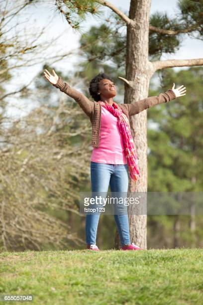 Woman reaches hands out to embrace nature.