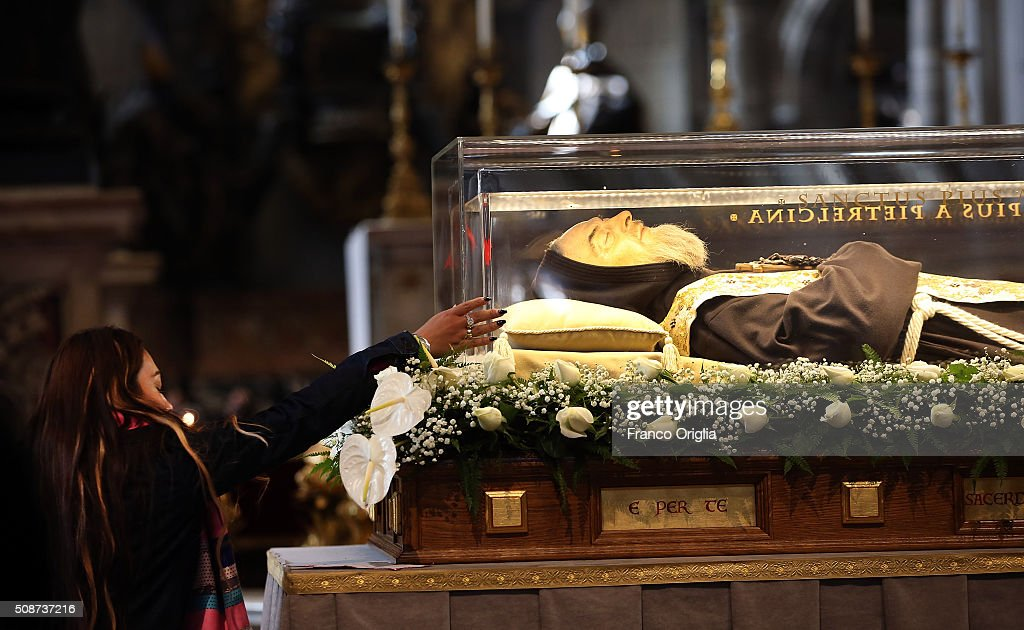 A woman reaches towards the corpse and relics of Padre Pio on display in St. Peter's Basilica for veneration by the faithful in connection with the ongoing Extraordinary Jubilee Year of Mercy on February 6, 2016 in Vatican City, Vatican. St. Pius of Pietralcina or San Padre Pio, as he is popularly known around the world was a Capuchin friar with a worldwide reputation during his earthly life as a mystic and miracle-worker, who was also a tireless confessor and laborer in favor of the poor, the sick, and the downtrodden.