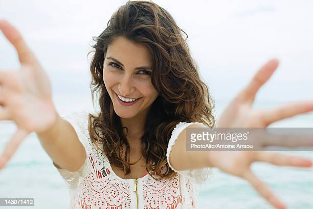 Woman reaching arms toward camera, smiling