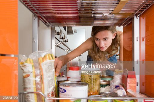 A woman reaching for a packet of food : Stock Photo
