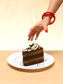 Woman reaching for a slice of cake