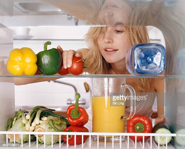 Woman Reaching For a Tomato in a Fridge