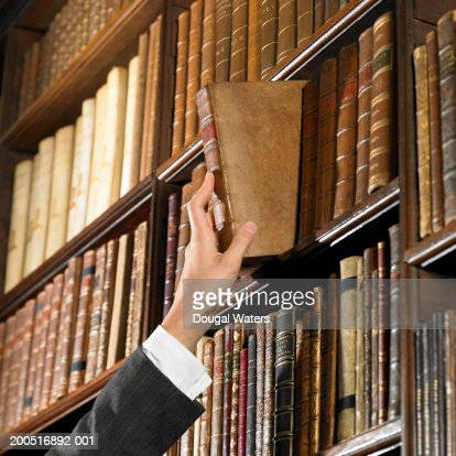 Woman reaching for book in library : Stock Photo