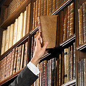 Woman reaching for book in library