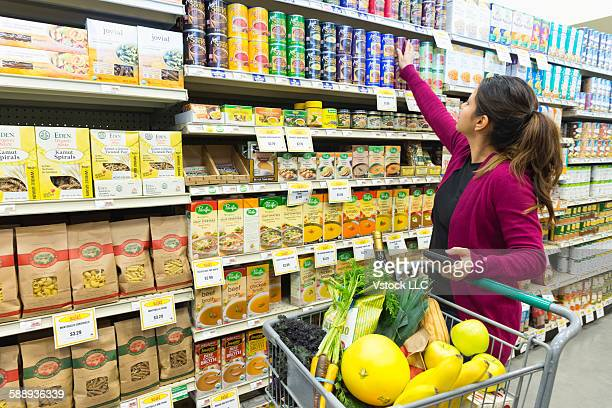 Woman reaching for canned food from supermarket shelf