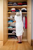 Woman Reaching for Clothes in Closet