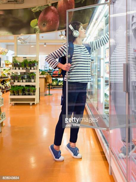 woman reaching for dairy produce in supermarket