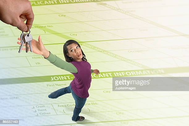 Woman reaching for keys while standing on loan application