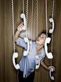 Woman reaching for suspended telephone receivers