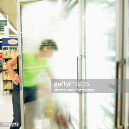 Woman reaching into freezer at grocery store