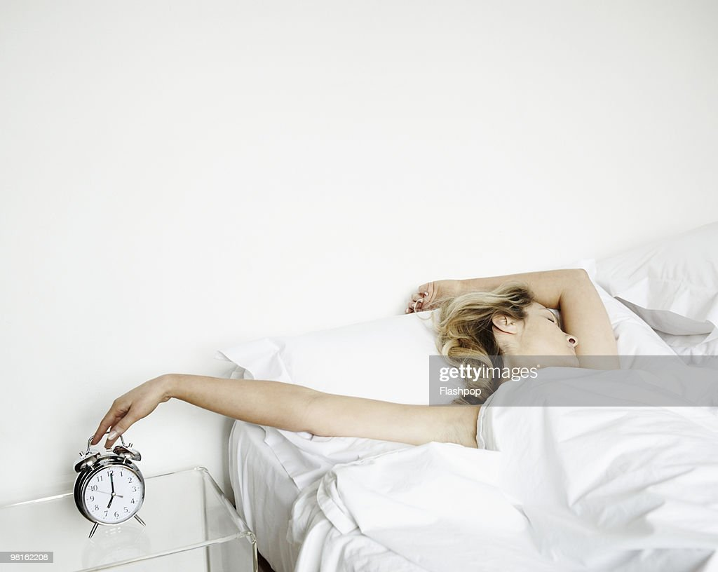 Woman reaching to turn alarm clock off