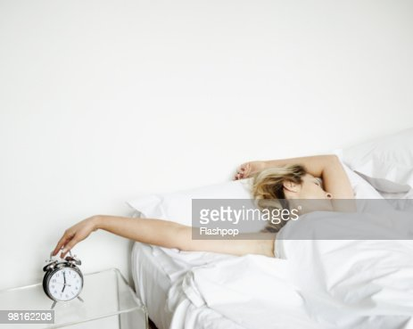 Woman reaching to turn alarm clock off