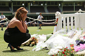 A woman reacts after placing flowers at the Randwick End of the SCG prior to the gathering of people to watch the funeral service held in Macksville...