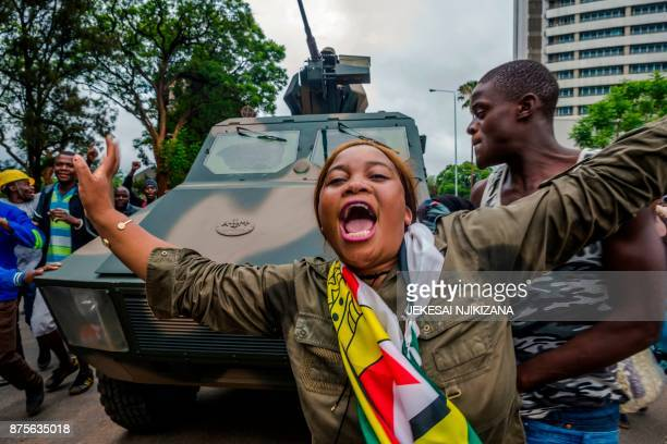 TOPSHOT A woman reacts as people march with an armored personnel carrier during a demonstration demanding the resignation of Zimbabwe's president on...