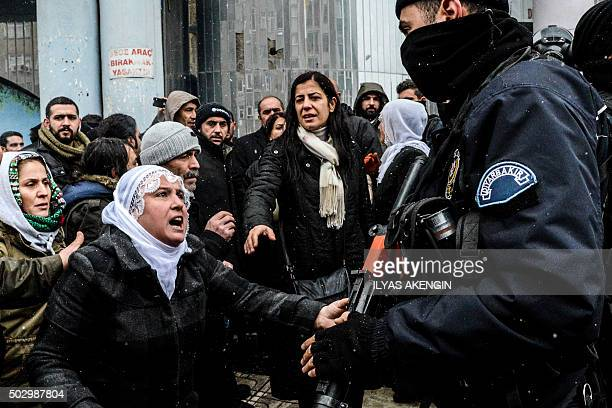 TOPSHOT A woman reacts as police officers stand guard on December 31 2015 in Diyarbakir during a demonstration after a curfew was lifted from the...