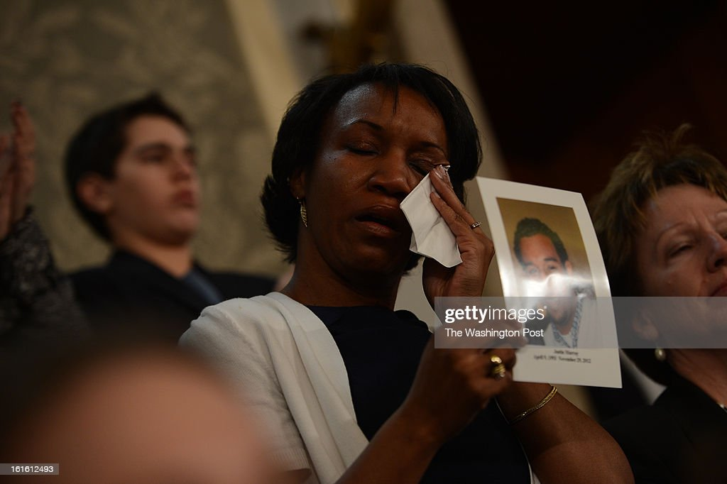 A woman reacts as she holds a photo of someone killed by gun violence as President Barack Obama speaks about gun violence during his address to a joint session of Congress as he gives his State of the Union address on Tuesday, February 12, 2013.
