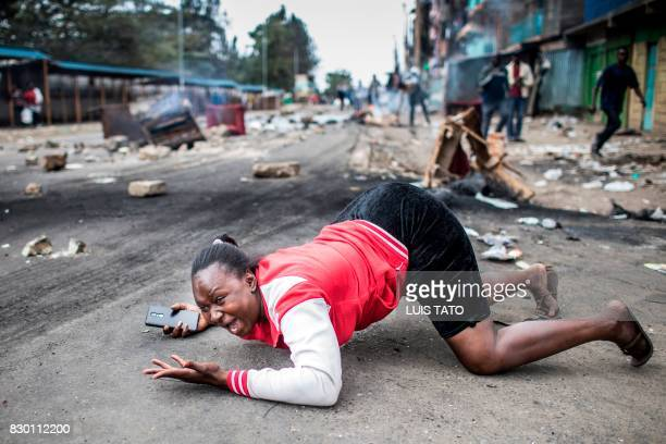 TOPSHOT A woman reacts as she passes Kenyan police troops during a protest by supporters of the National Super Alliance presidential candidate on...