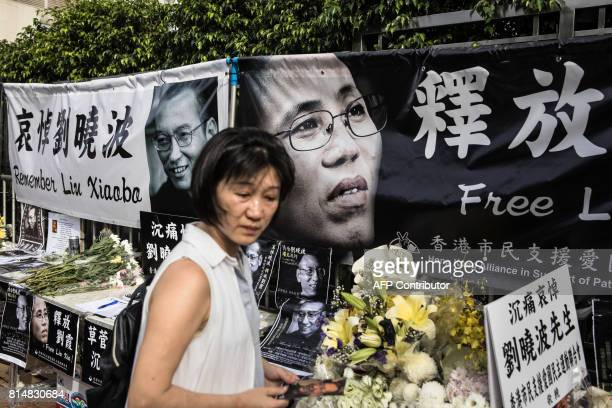 A woman reacts as she visits a makeshift memorial for the late Chinese Nobel laureate Liu Xiaobo outside the Chinese Liaison Office in Hong Kong on...