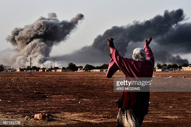 A woman reacts as smoke rises from the the Syrian town of Ain alArab known as Kobane by the Kurds after a strike from the USled coalition as it seen...