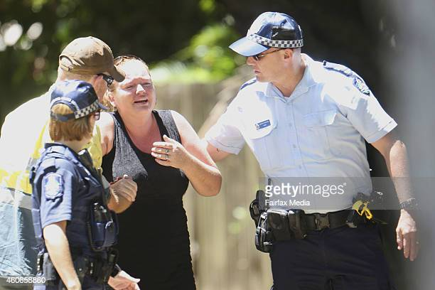 A woman reacts at the scene of a mutliple stabbing in the suburb of Manoora on December 19 2014 in Cairns Australia Eight children have been found...