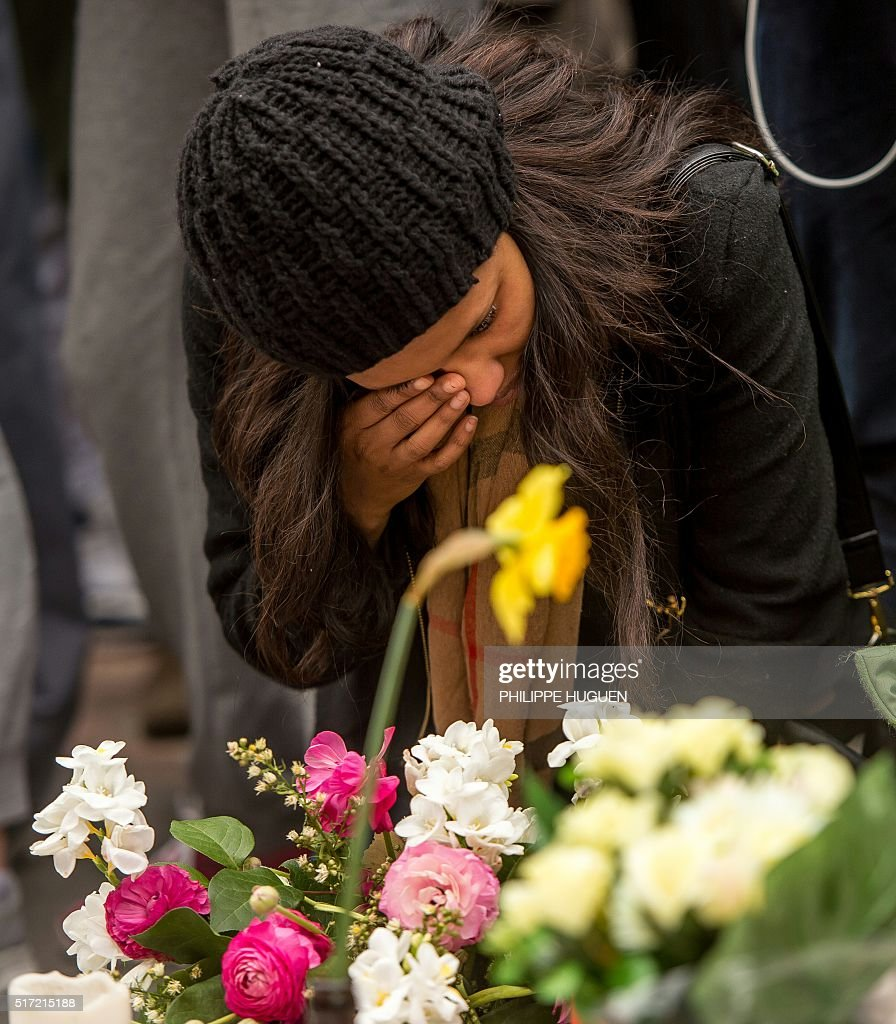 woman reacts during a minute of silence held at a makeshift memorial ...