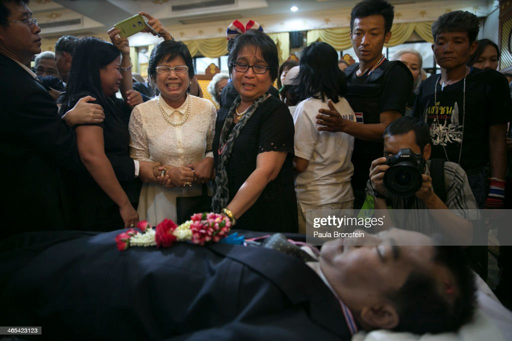 A woman reacts emotionally as hundreds of mourners pay their respects over the body of Sutin Tharatin, a core anti-government leader who was killed by gunmen yesterday, on January 27, 2014 in Bangkok, Thailand. Nine others were also injured during election related violence as protesters blocked polling stations as advanced voting took place in the capitol city. Bangkok Shutdown has been in effect for two weeks as the anti-government protesters continue to block major intersections. The Thai government imposed a 60-day state of emergency in Bangkok and the surrounding provinces in an attempt to cope with the on-going political turmoil but so far this decree has had no effect on the mass protests.