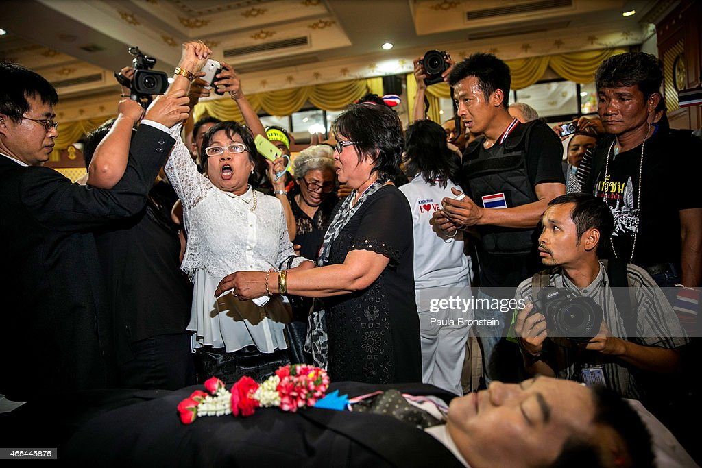 A woman reacts emotionally as hundreds of mourners pay their respects over the body of Sutin Tharatin, a core anti-government leader who was killed by gunmen yesterday in Bangkok on January 27, 2014 in Bangkok, Thailand. Nine others were also injured during election related violence as protesters blocked polling stations as advanced voting took place in the capital city. Bangkok Shutdown has been in effect for two weeks as the anti-government protesters continue to block major intersections. The Thai government imposed a 60-day state of emergency in Bangkok and the surrounding provinces in an attempt to cope with the on-going political turmoil but so far this decree has had no effect on the mass protests.