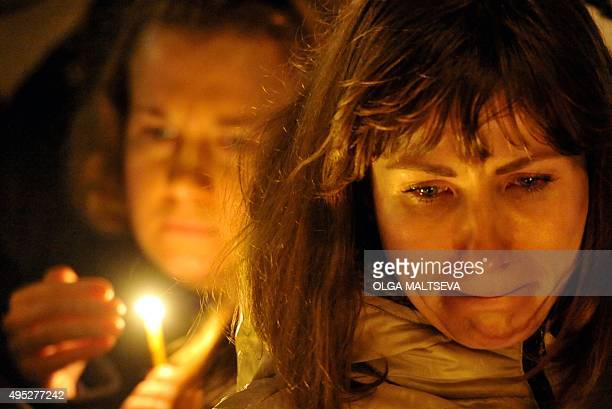 A woman reacts in central Saint Petersburg on November 1 as people gather to light candles in memory of the victims of a jetliner crash Flags flew at...