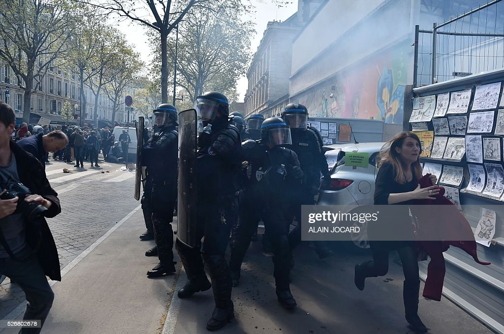 A woman reacts next to French anti riot police during a clash with protesters during the traditional May Day demonstration in Paris on May 1, 2016.