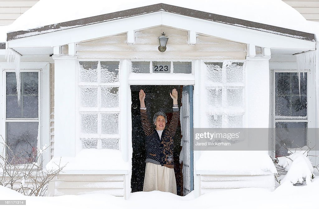 A woman reacts to the snow after opening her front door on February 9, 2013 in Boston, Massachusetts. The powerful storm has knocked out power to 650,000 and dumped more than two feet of snow in parts of New England.