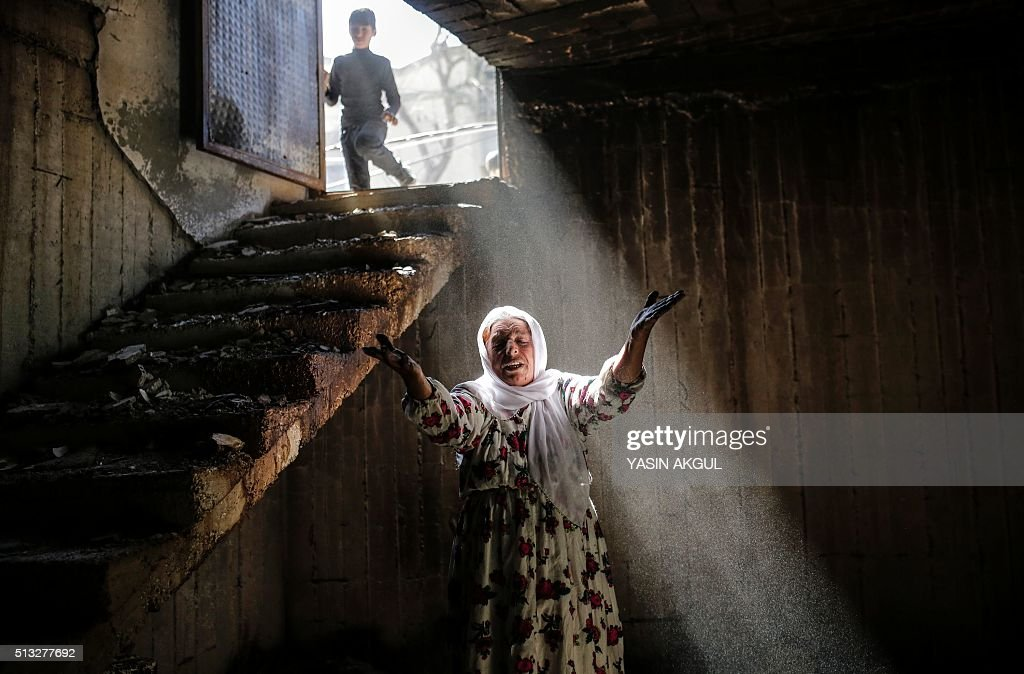 TOPSHOT A woman reacts while walking among the ruins of damaged buildings following heavy fighting between government troops and Kurdish fighters on...
