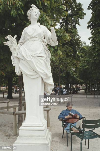 A woman reading a book at Tuileries Garden Paris France August 1999