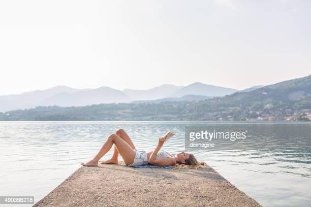 Mujer leyendo un libro junto al lago