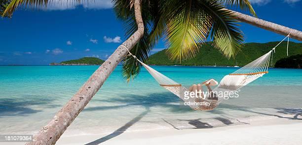 Frau liest ein Buch in der Hängematte am Strand am Karibischen Meer