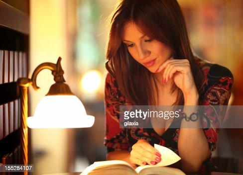 Femme lisant un livre dans la bibliothèque.