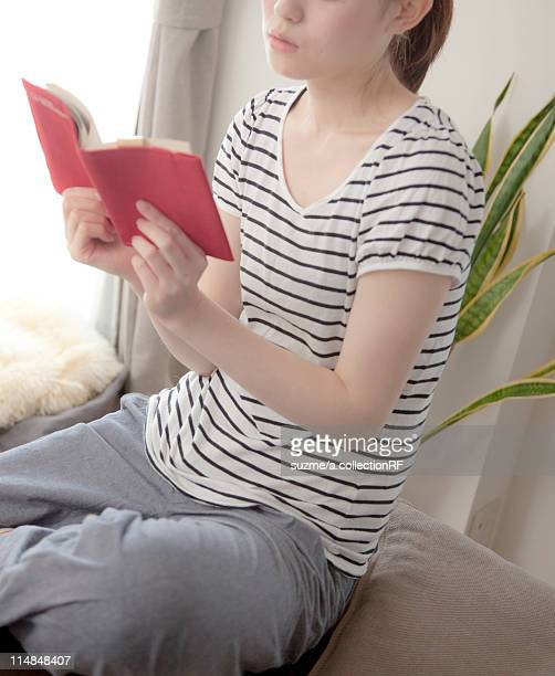 Woman reading a book in living room