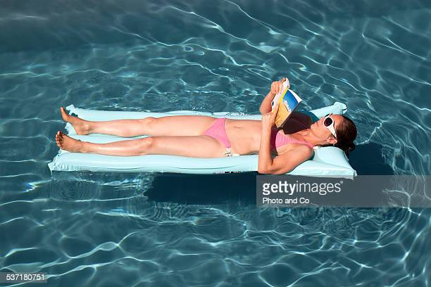 woman reading a book in the pool