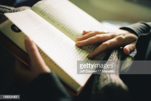 Woman reading a book, indoor light, hands close-up : Stock Photo