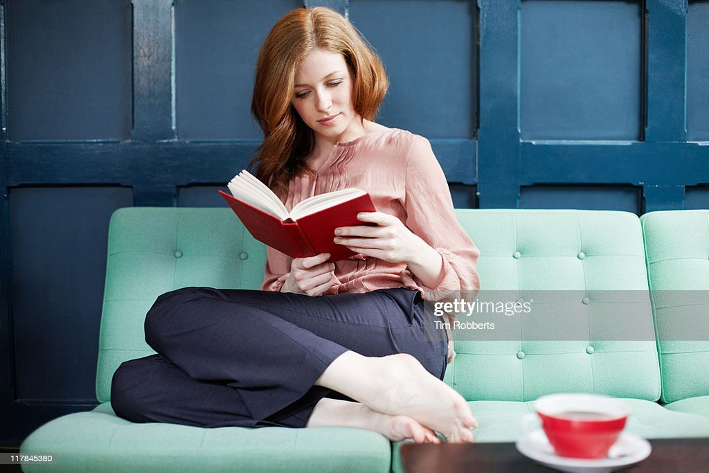 Woman reading a book on sofa. : Stock Photo