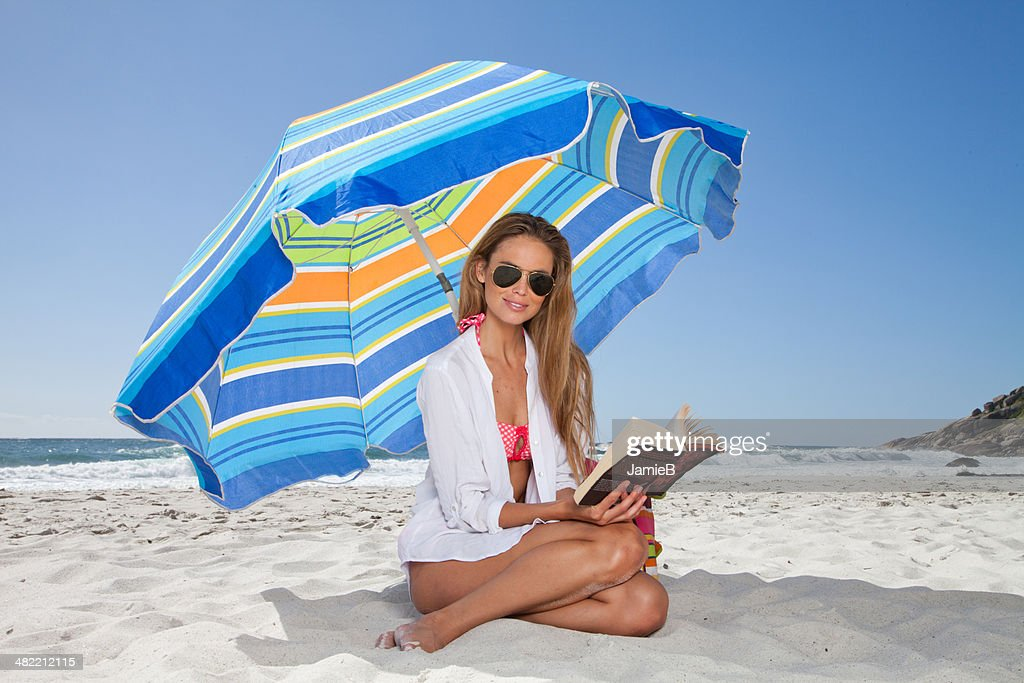 Young woman on beach with a book