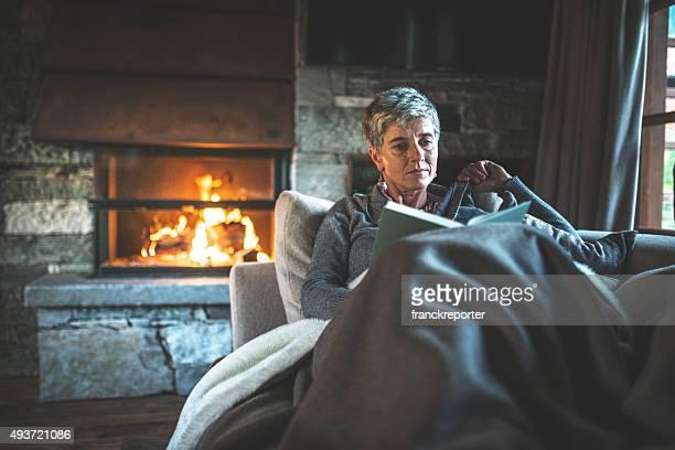 Femme lisant un livre sur le canapé