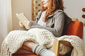 Happy young woman reading a book in a chair