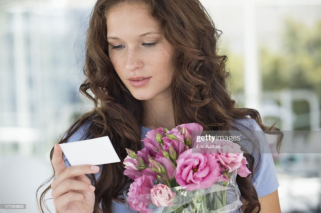 Woman reading a card with bouquet of flowers : Stock Photo