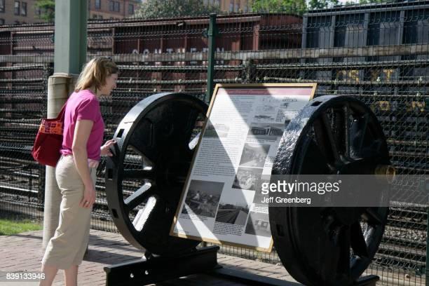A woman reading a historical marker at David R and Susan S Goode Rail walk